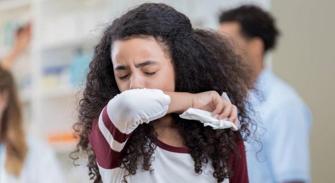 Garota coloca o braço na frente do rosto ao espirrar