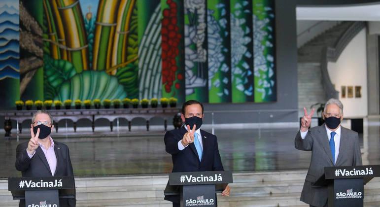 """O governador de São  Paulo (ao centro), faz gesto de """"V"""", de vacina, segundo ele próprio propôs."""