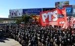 Polícia anti-motim monta guarda enquanto os manifestantes bloqueiam uma estrada durante uma greve nacional de um dia em Buenos Aires