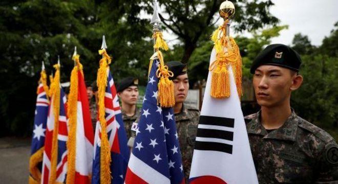 Soldados erguem bandeiras de países que lutaram na Guerra da Coreia