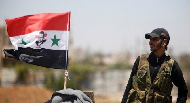 Soldado do Exército posa ao lado de bandeira da Síria em Deraa