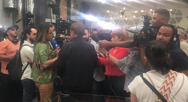 Apresentador (de costas) é cercado por jornalistas no lançamento do reality