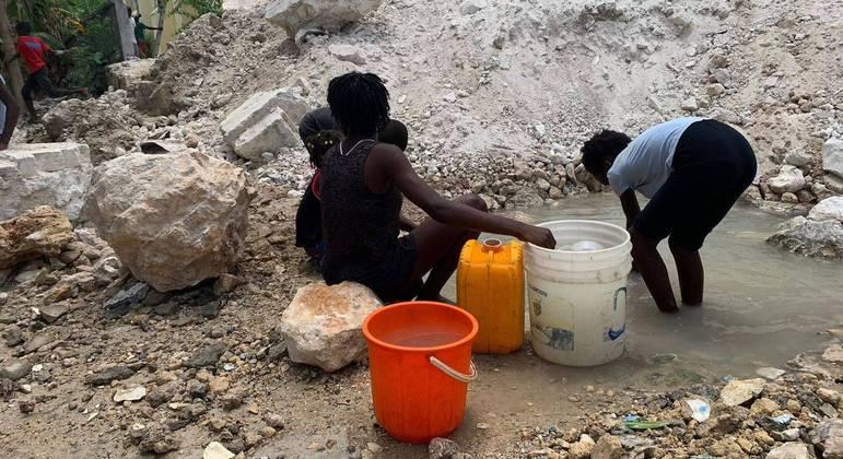 Crianças pegam água ao lado de igreja desmoronada após terremoto em Corail, no Sudoeste do Haiti
