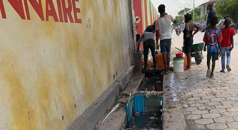 Bica de água em muro do estádio, ao lado de fosso sujo, utilizada para beber e para lavar panelas em Les Cayes