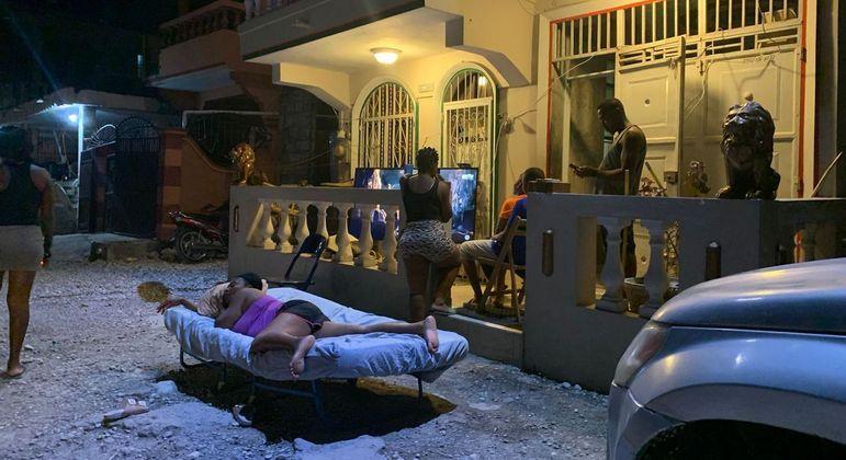 Mulher dorme na rua, à noite, em Les Cayes, cidade atingida por terremoto no Haiti