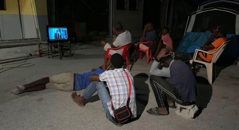 Homens se juntam para assistir novela coreana em Les Cayes, enquanto mulheres dormem em tendas