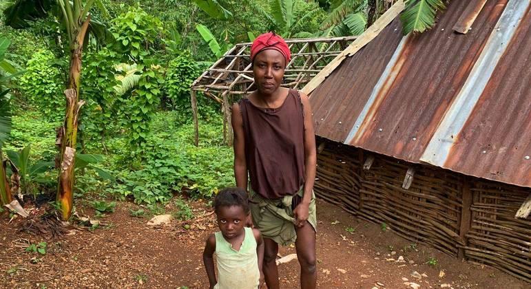 A agricultora Gislaine Jules, com sua filha, em frente à casa onde vivia antes do terremoto de 14 de agosto