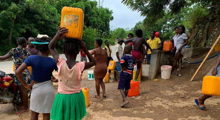 Com risco de contaminação em rios, haitianos precisam de doações de água para tarefas básicas