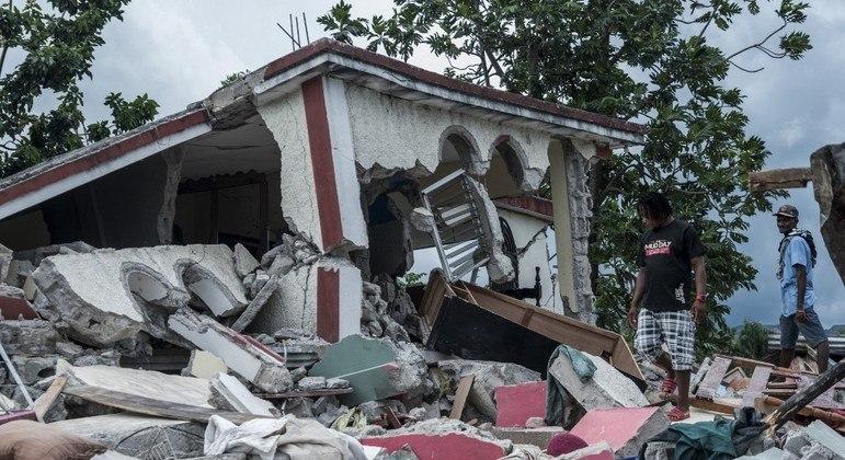 Pessoas vasculham destroços de casas destruídas pelo terremoto em Camp Perrin