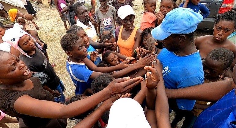 Crianças e mulheres disputam balas distribuídas a partir das mãos do homem com boné azul