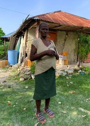 Cima Gladys, 57, em frente à casa onde mora e onde continua dormindo
