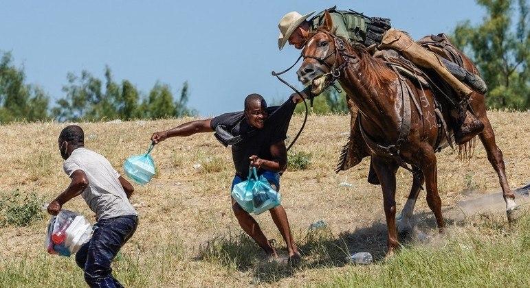 Haitianos perseguidos  por agente fronteiriço dos Estados Unidos