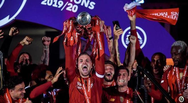 O capitão Henderson ergue a taça da Premier League para o Liverpool