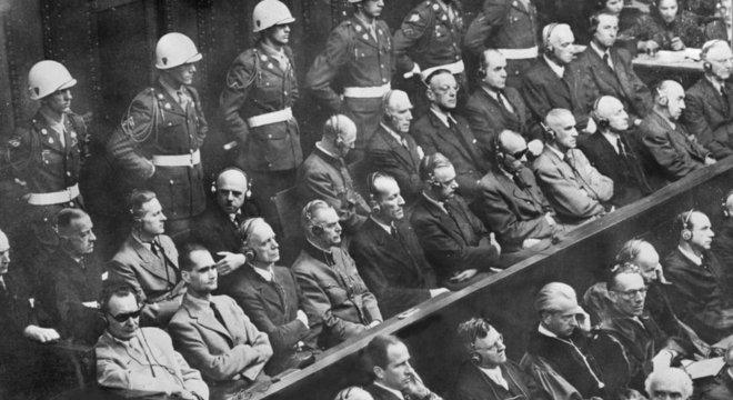 Os julgamentos de Nuremberg começaram em 20 de novembro de 1945. No canto inferior esquerdo, usando óculos escuros, está Hermann Göring, seguido por Rudolf Hess, os réus mais notórios