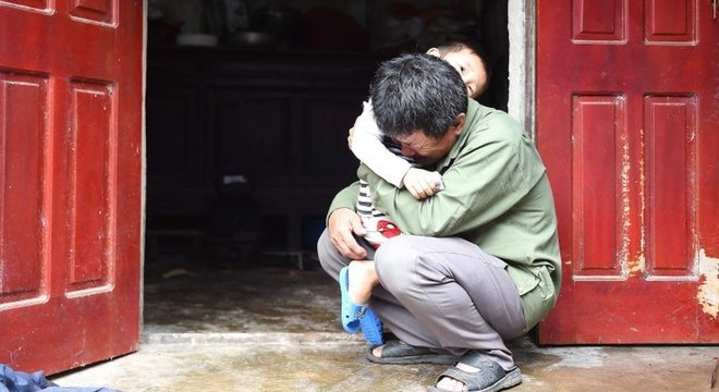Le Minh Tuan abraça seu neto. Ele espera que seu filho não esteja entre os mortos