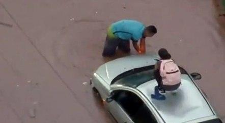 Motorista amarra corda para tentar tirar carro ilhado em alagamento na zona oeste de São Paulo