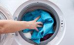 Homem colocando roupa para lavar.