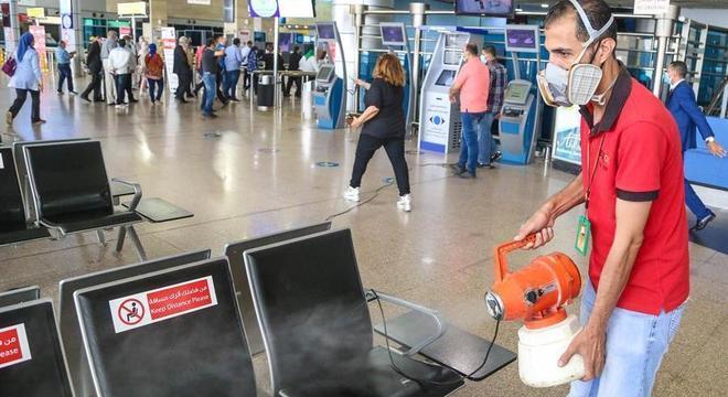 Homem desinfeta cadeiras do aeroporto do Cairo, no Egito, contra o coronavírus
