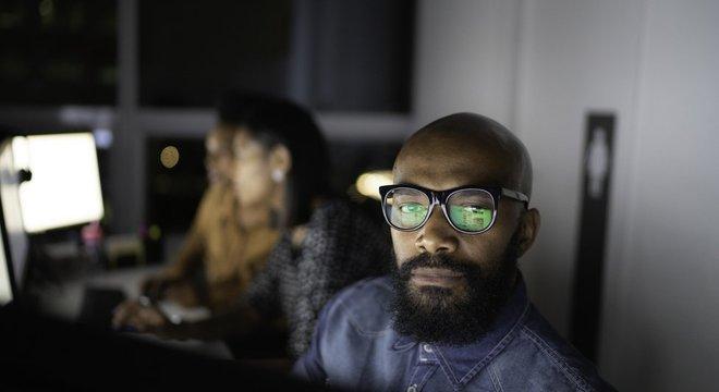 Homem e mulheres no pano de fundo com rostos iluminados por telas de computador em escritório à noite