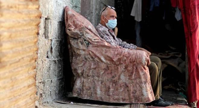 Homem usando máscara se senta do lado de fora em campo de refugiados, em Gaza