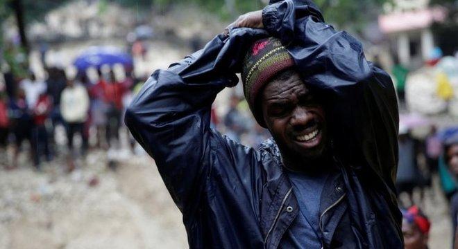 Homem se desespera ao ver corpo de sua mãe, morta após a tempestade Laura, em Porto Príncipe
