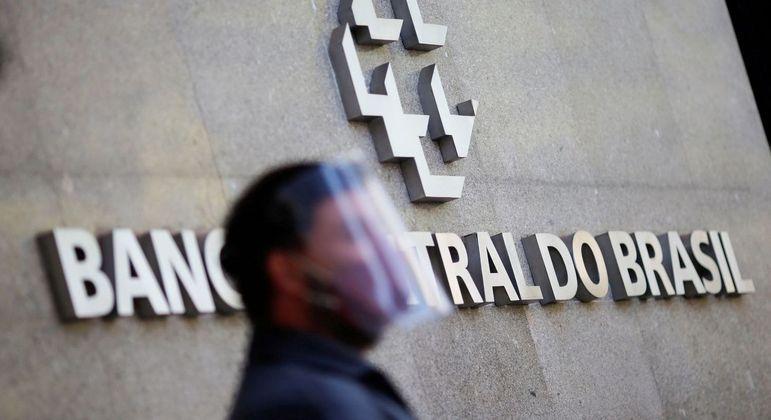 Homem usa máscara de proteção em frente à sede do Banco Central, em Brasília