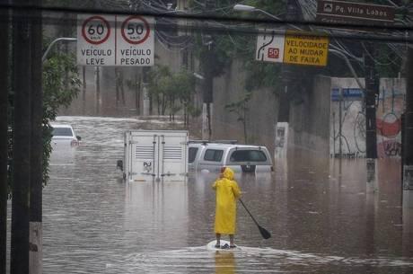 Homem usa stand up paddle para socorrer pessoas ilhadas