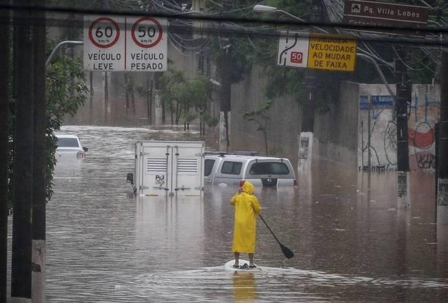 Homem usa stand up paddle para socorrer pessoas ilhadas pela enchente próximo à Ponte do Jaguaré