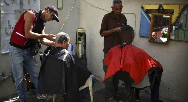 Homens cortando os cabelos em salão de Caras, na Venezuela