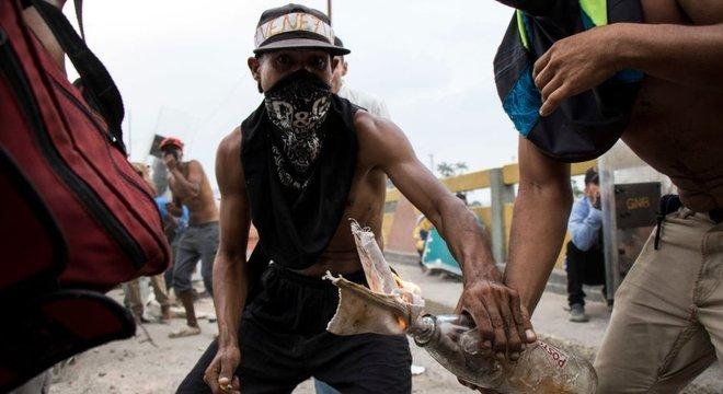 Homens encapuzados protestam durante tentativa de entrada de ajuda humanitária na Venezuela, no fim de semana