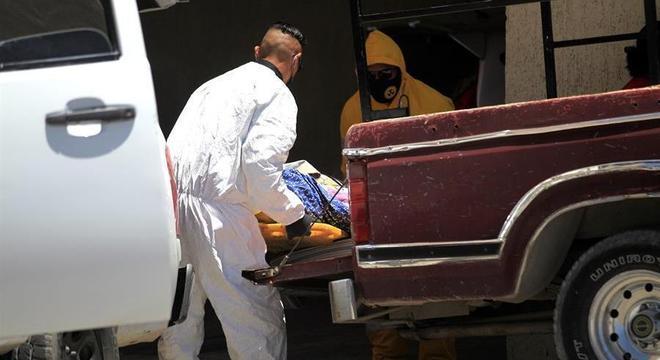 Homens retiram corpo de morto pela covid-19 em Ciudad Juarez, no México