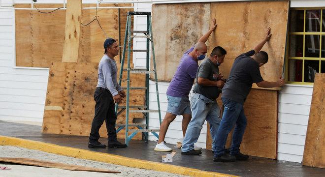 Homens cobrem janela de restaurante em Cancún para passagem de furacão