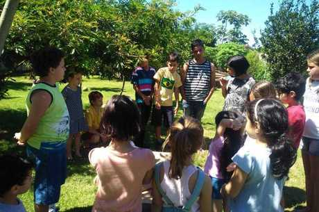 As crianças interagindo em uma aula ao ar livre