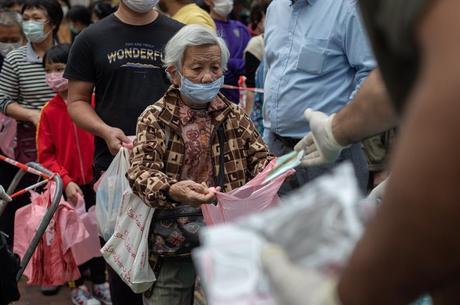 idosos aguardam a distribuição de máscaras faciais gratuitas no distrito de Sham Shui Po, em Hong Kong