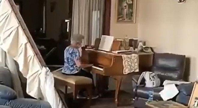 May Abboud Melki toca piano na sala destruída de seu apartamento em Beirute