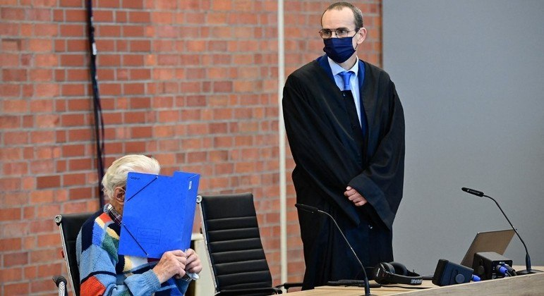 Réu Josef S. senta-se ao lado de seu advogado Stefan Waterkamp e esconde seu rosto enquanto aguarda o julgamento
