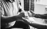Foto em preto e branco das mãos entrelaçadas de dois idosos