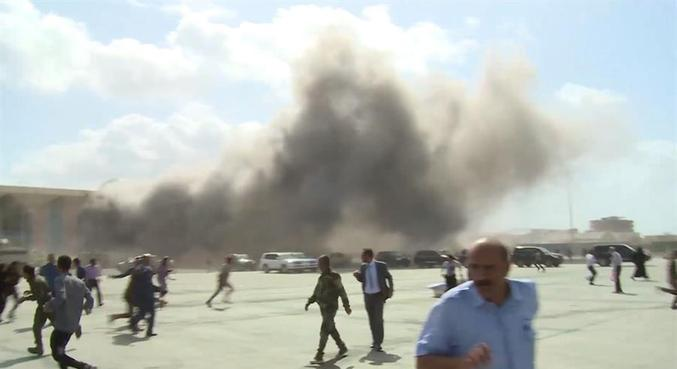 Pessoas correm após explosões na pista do aeroporto de Aden, no Iêmen