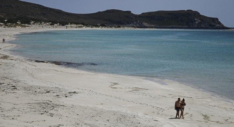 Casal caminha pela areia da praia da ilha Elafonisos, na Grécia
