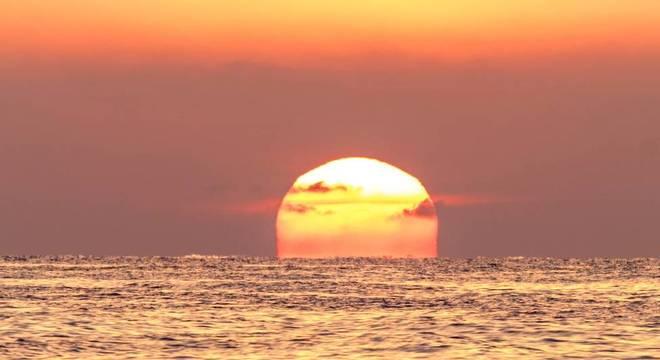 O sol pode ficar vermelho sobre o mar e com um céu laranja