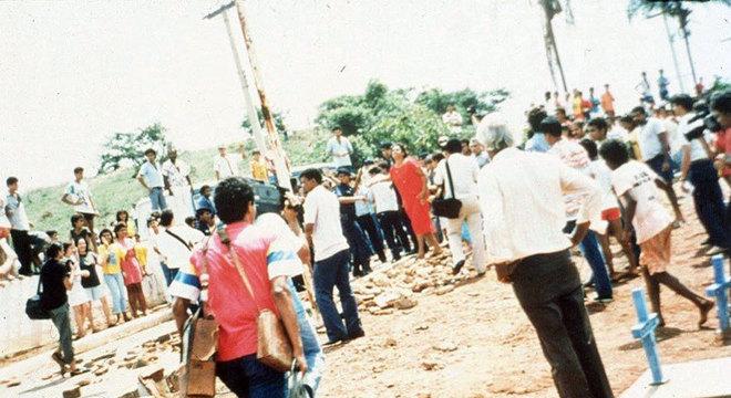 Pessoas em cemitério durante enterro das duas primeiras vítimas