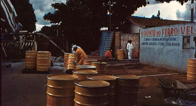 Imagem mostra toneis posicionados em frente a ferro-velho contaminado