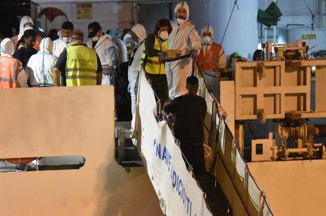 Imigrantes deixam barco em porto da Itália