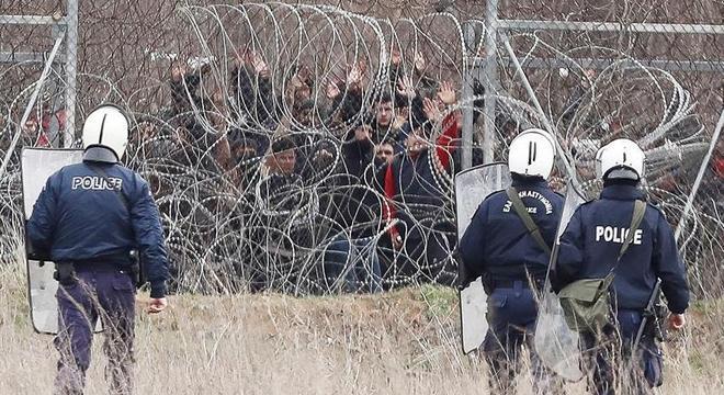 Imigrantes fazem sinal de que se rendem à policiais na fronteira Grécia-Turquia