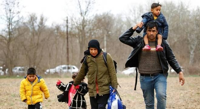 Família de refugiados cuzando a fronteira entre a Turquia e a Grécia