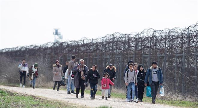 Família caminha junto à cerca que divide a fronteira com a Grécia em Erdine, na Turquia