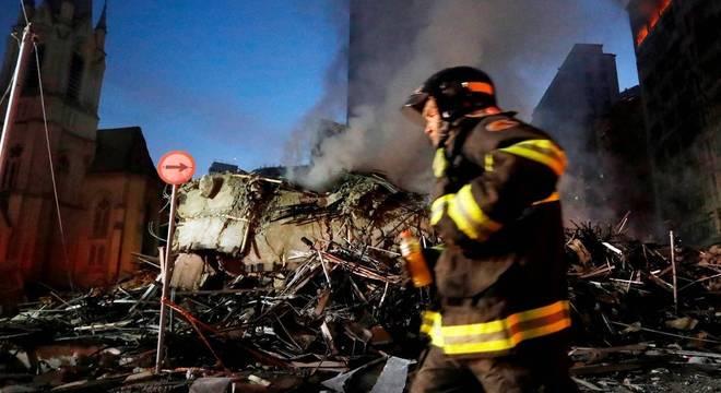 Bombeiro trabalha no local onde prédio desabou na madrugada desta terça (1)