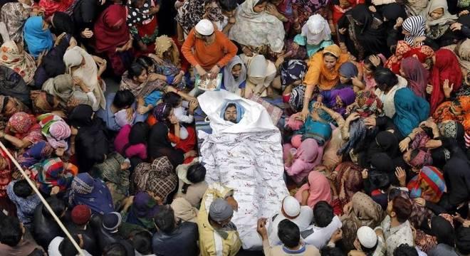 Pessoas cercam o corpo de um dos mortos nos confrontos entre hindus e muçulmanos