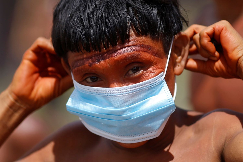 Indígena do povo ianomâmi segura máscara de proteção em Alto Alegre, Roraima