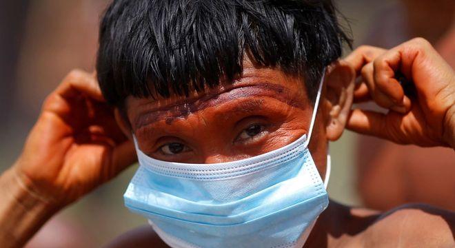 Indígena do povo ianomâmi segura máscara de proteção em Alto Alegre (RR)